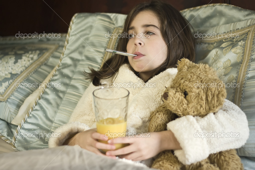 Young girl who is in bed sick, with thermometer in mouth and holding a glass of juice. — Stock Photo #4485246