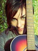 Beautiful green eyes girl with guitar — Stock Photo