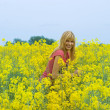Blond with pink t-shirt in yellow field - Stock Photo