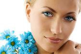 Blue eyes and blue daisy — Stock Photo