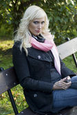 Blond girl sitting in a bench — Stock Photo