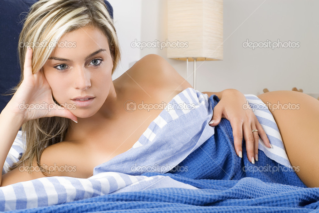 A sexy and cute blond girl between blue sheet in a bedroom — Stock Photo #4701112