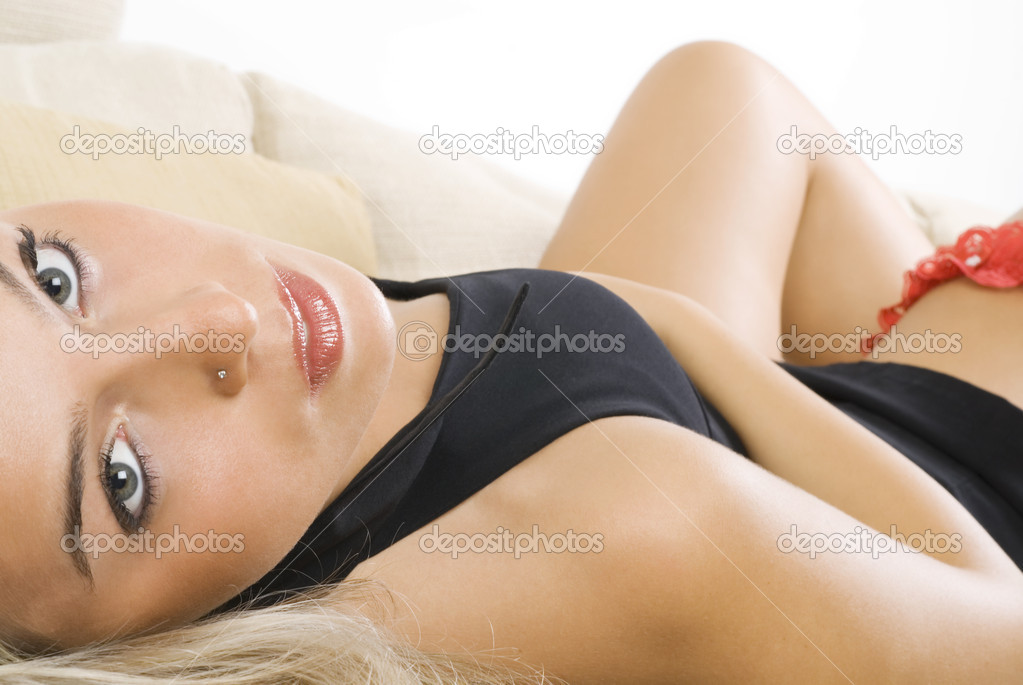 Pretty blond girl in black dress and red garter laying down on a beige sofa — Stock Photo #4701259