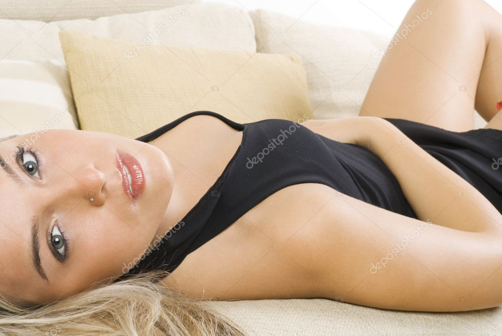 Pretty blond girl in black dress and red garter laying down on a beige sofa — Stock Photo #4701260