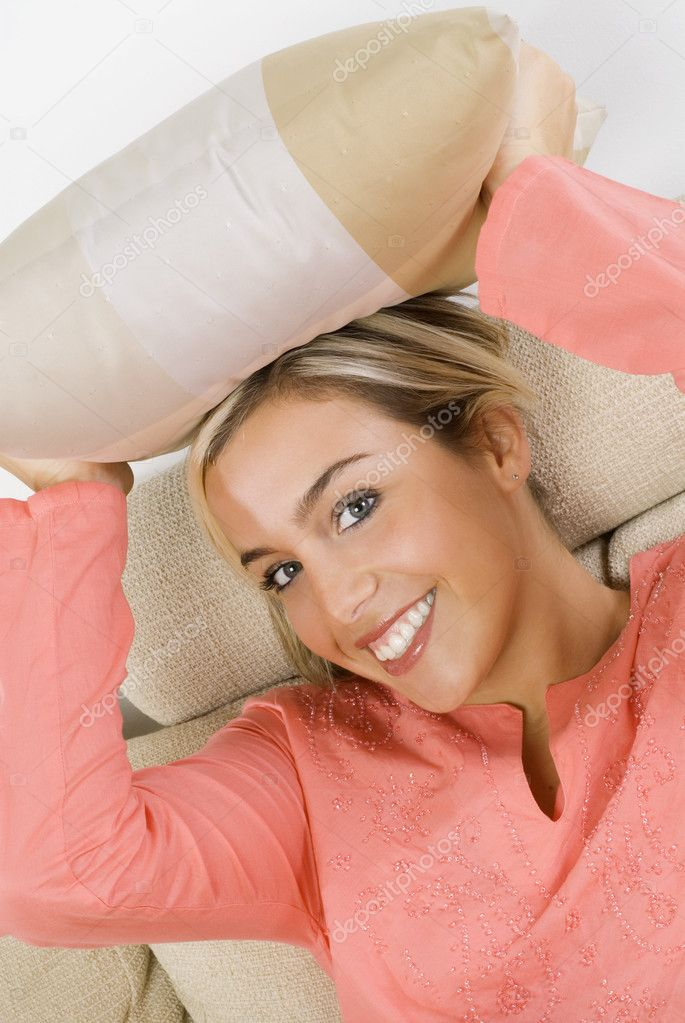 Portrait of a pretty blond female wearing evening pink gown sitting on sofa with braids and arming a pillow — Stock Photo #4701270