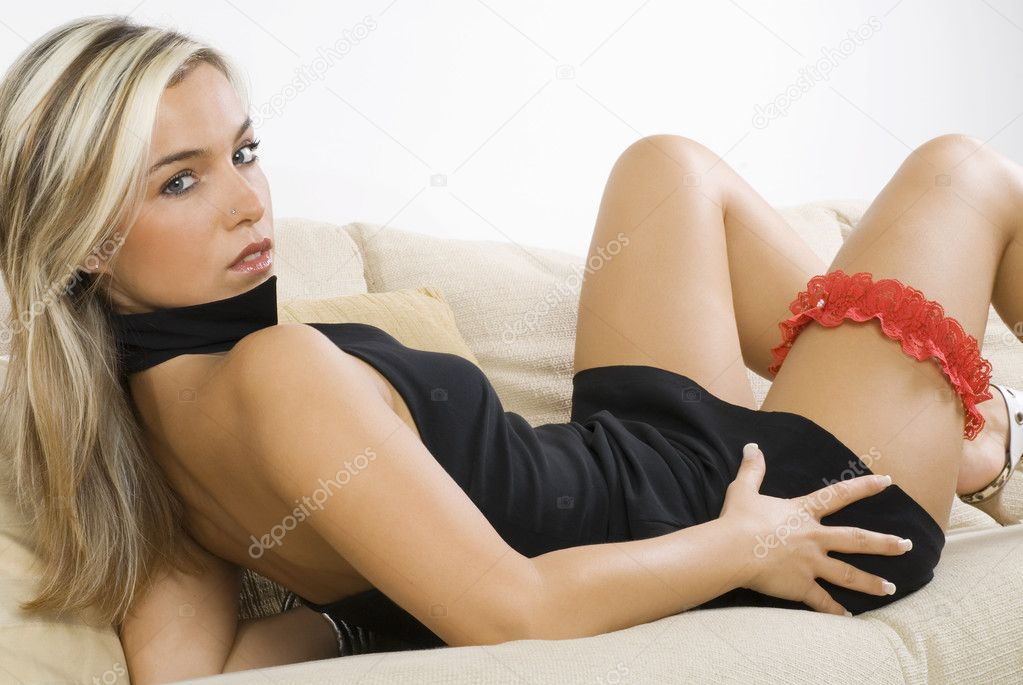 Pretty blond girl in black dress and red garter laying down on a beige sofa — Stock Photo #4701288