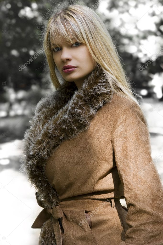 Beautiful blond girl with winter jacket with fur in a park in a sunny winter day  Stock Photo #4701598