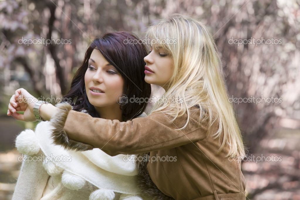 Two nice girl looking at the time in park during a winter day — Foto Stock #4701605