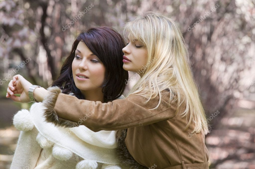 Two nice girl looking at the time in park during a winter day — Stock fotografie #4701605