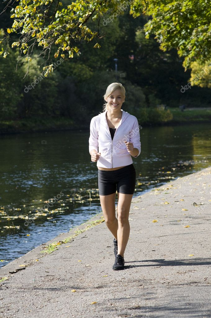 Pretty young blond girl running in the park near river — Stock Photo #4701660