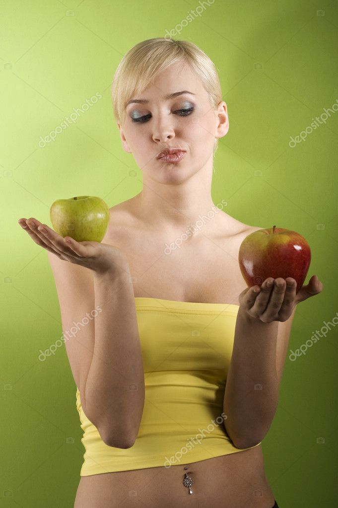 Blond girl with red and green apple in act to take a decision of what kind of apple to eat red or green  Foto Stock #4702108