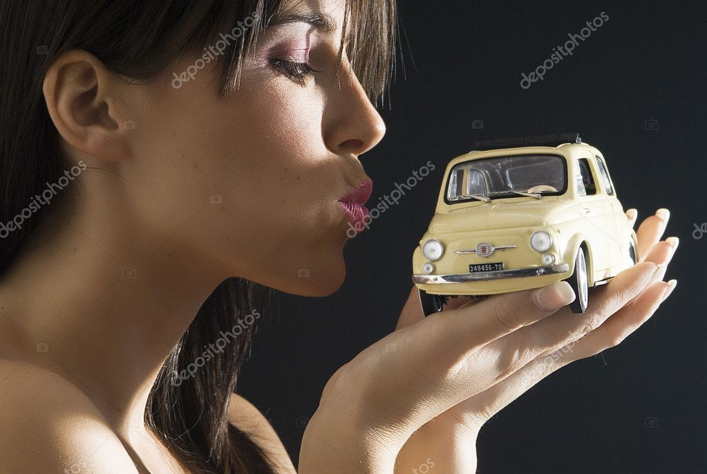 Nice and young brunette kissing with an italian style car,fiat 500  Stock Photo #4702727