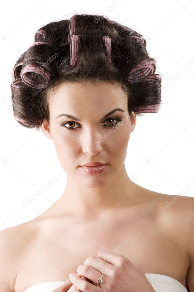 Beauty portrait of a young brunette woman with hair curlers in her hair — Stock Photo #4703435