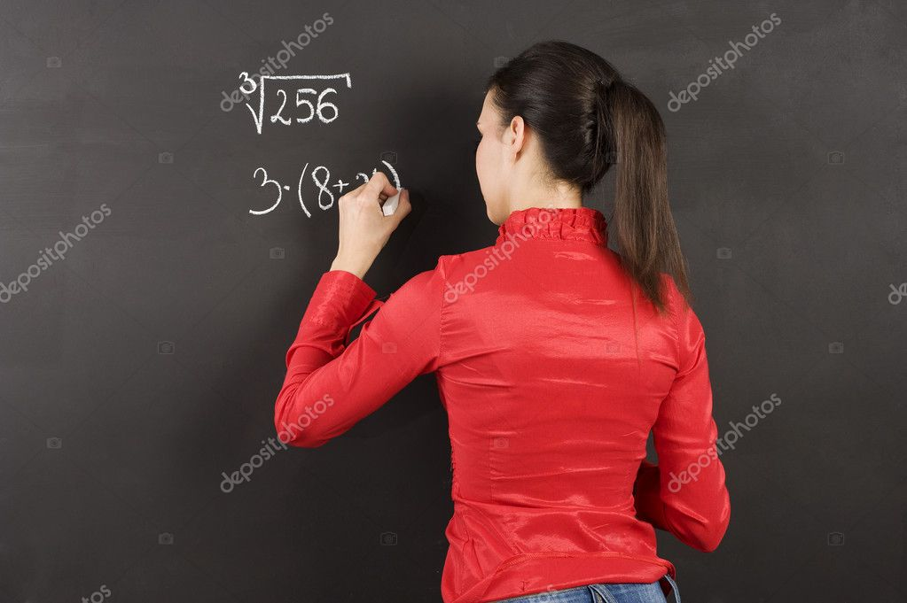 Pretty young college student writing on the chalkboard/blackboard during a math class — Stock Photo #4703490