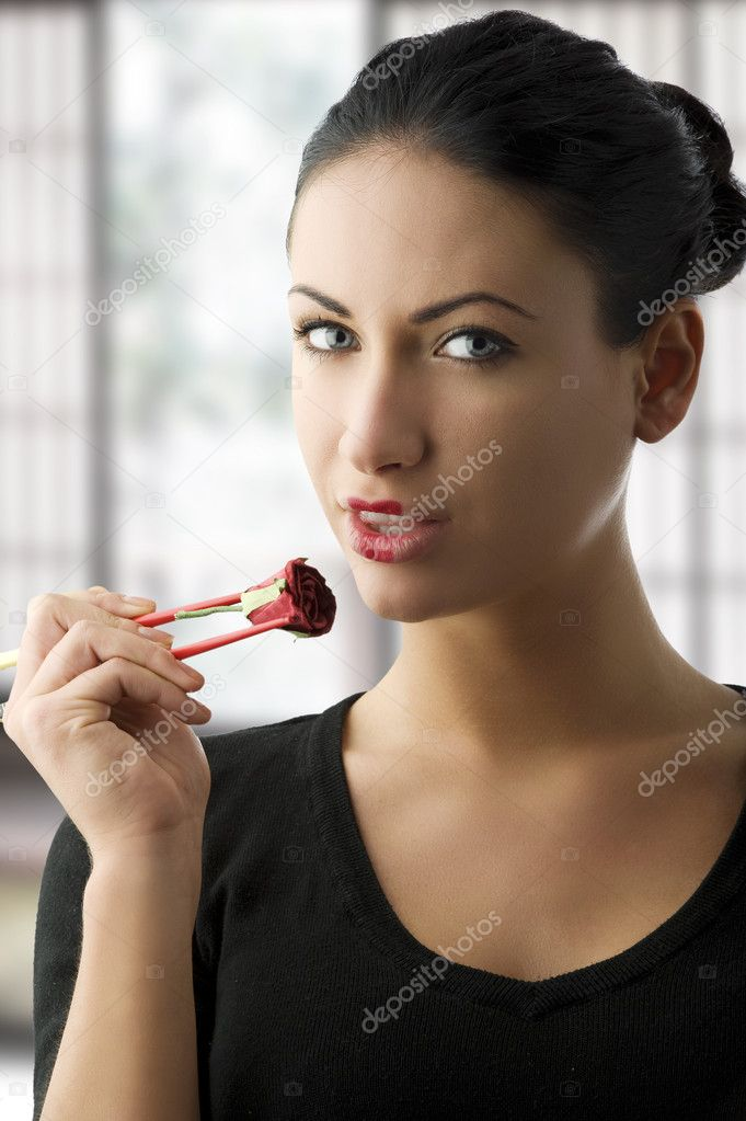 Beautiful brunette with japanese muouth and a rose between chopsteck — Stock Photo #4704082