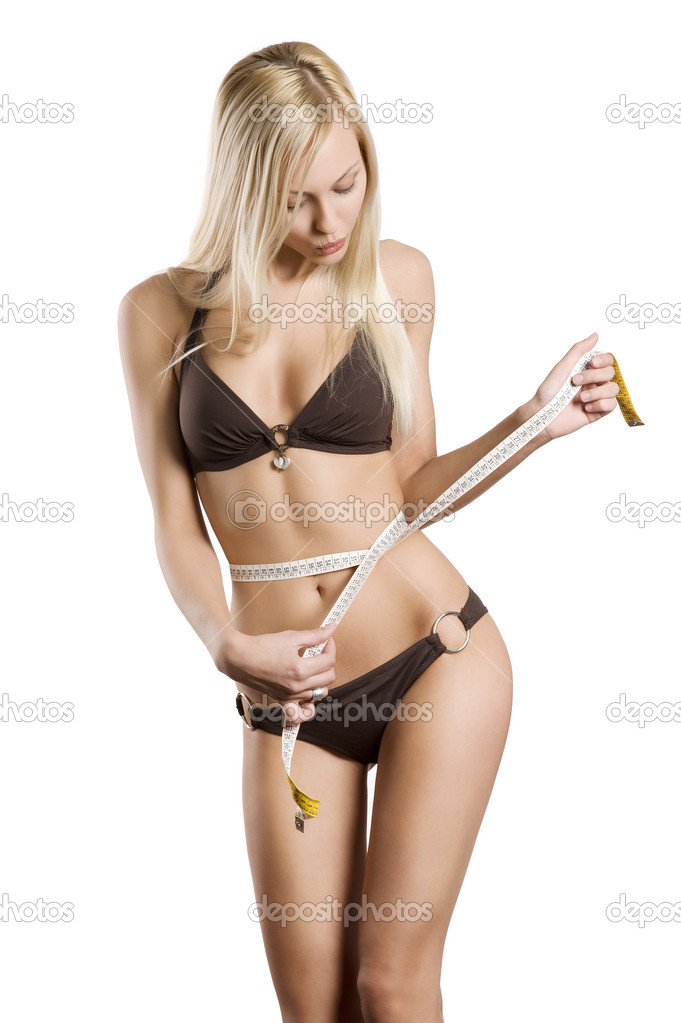 Young blond woman measuring her body with a tape looking down and making face — Stock Photo #4704806