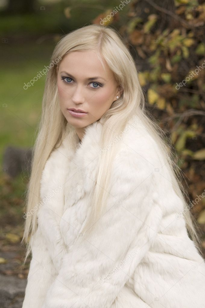 Very nice girl wearing a white fur in a winter day in park — Stock Photo #4705712