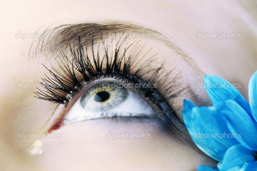 Closeup of the eye of woman with creative eyelashes and blue petals — Stock Photo #4705790
