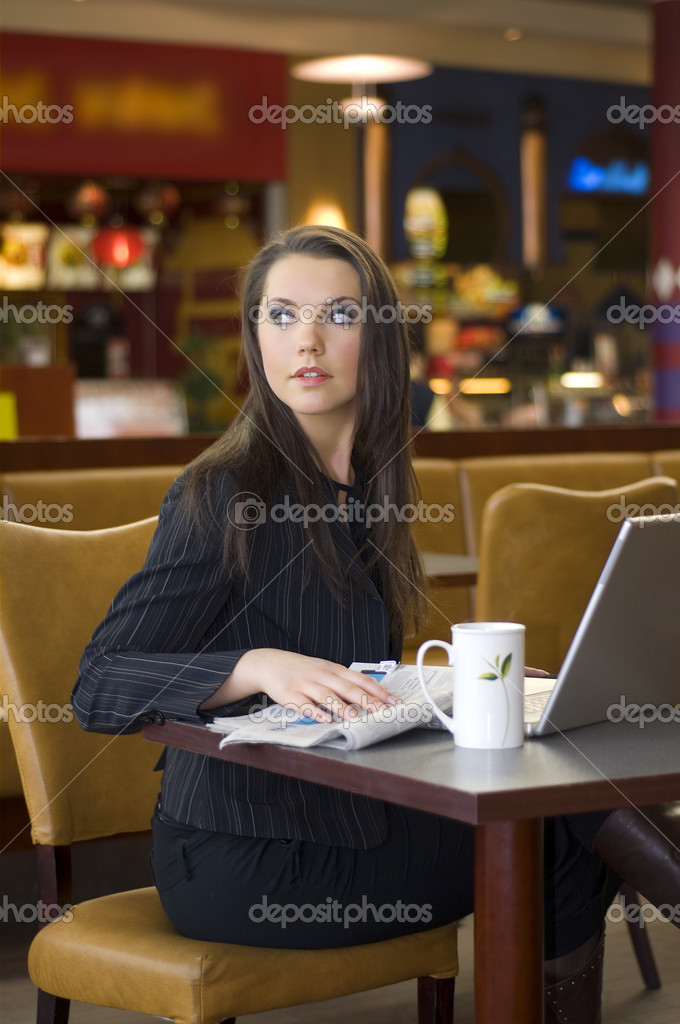 Beautiful young woman sitting in a bar with laptop and tea  Stock Photo #4706387