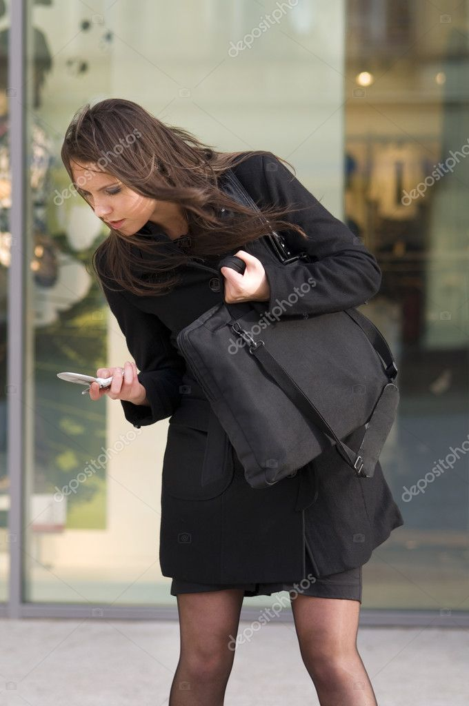 Nice girl outside near a shop window trying to answer to mobile — Stock Photo #4706408