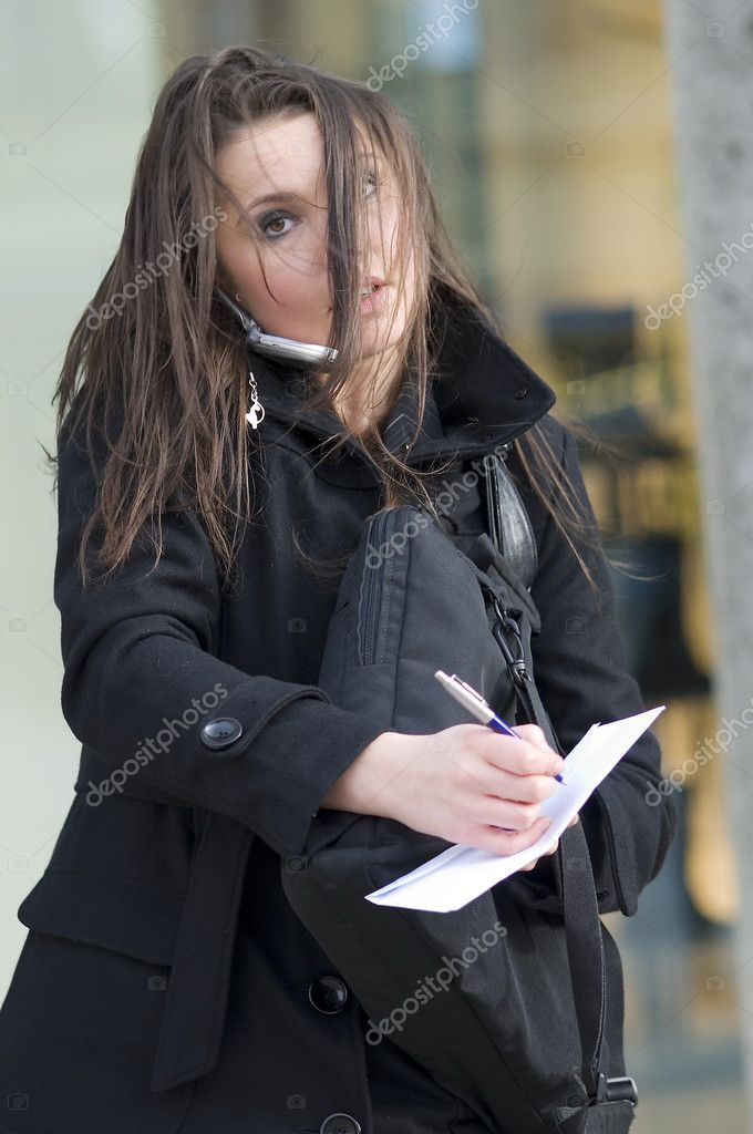 Girl with hair in the wind writing notes looking in trouble — Stock Photo #4706413