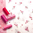 Pink spools of thread on a floral fabric - Stock Photo