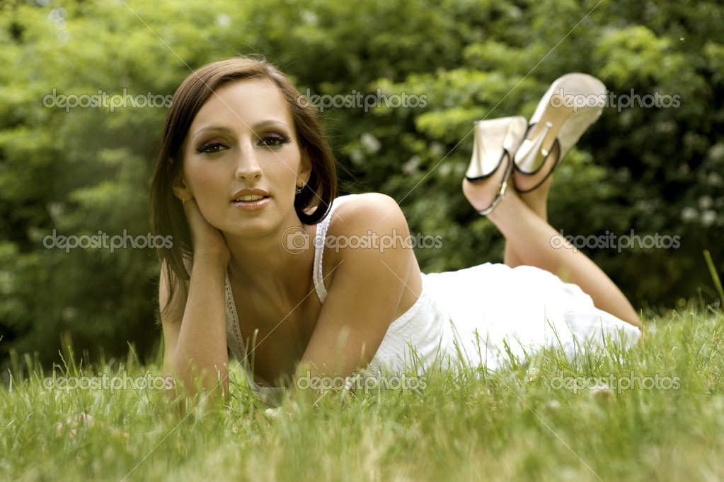 Beautiful and sexy brunette girl on the grass in the park — Stock Photo #4432554