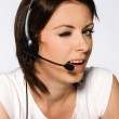 Beautiful girl with dark hair with headphones and microphone wearing white — Stock Photo