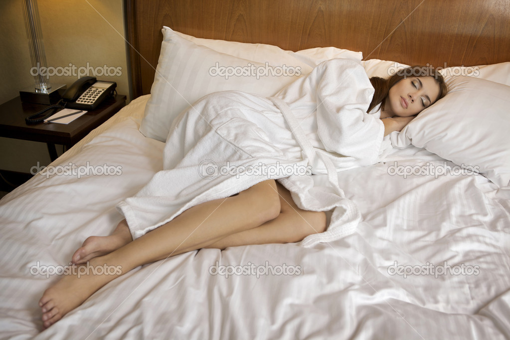 Beautiful brunette woman is resting on white bed — Stock Photo #4751374