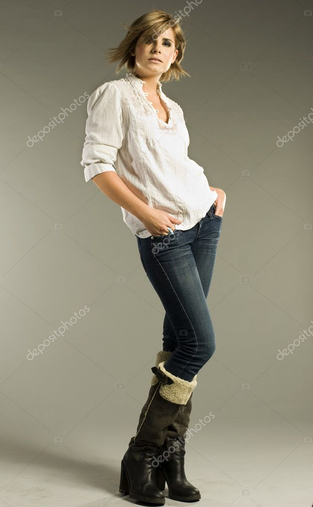 Beautiful blonde model wearing white shirt, jeans and boots on grey background — Stock Photo #4808761