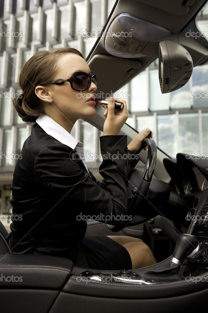 Attractive and young businesswoman putting on lipstick in a cabrio car — Stock Photo #4809513
