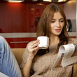 Mid adult woman drinking coffee and reading news — Stock Photo #4917174