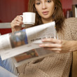 Mid adult woman drinking coffee and reading news - Stock Photo