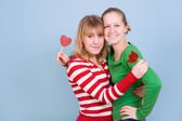 Two beautiful girls with red candies — Stock Photo
