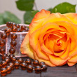 Yellow rose and beads — Stock Photo