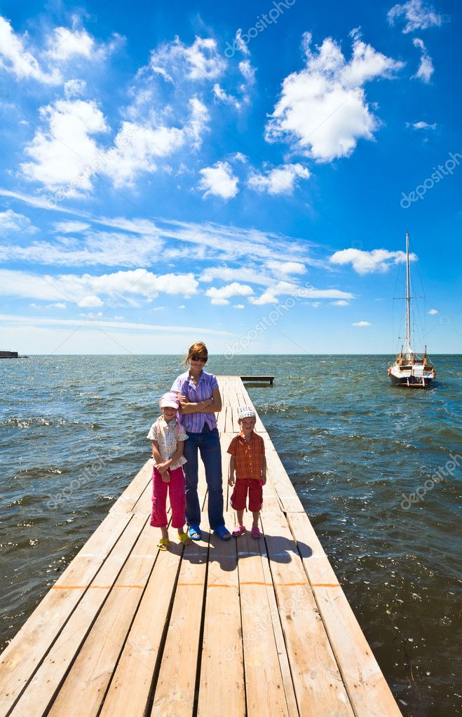 Family (mother with two children) on wooden pier and yacht near  Stock Photo #4471540