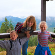 Family on wooden mountain cottage porch — Stock Photo #4513869