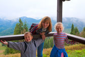 Family on wooden mountain cottage porch — Stock Photo