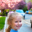 Happy small girl portrait and blossoming japanese cherry tree — Stock Photo