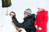 Family sculpting snowmen in winter park — Stock Photo