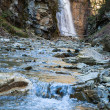 Waterfall and brook in mountain forest ravine - Stock Photo