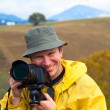 Happy photographer on autumn mountain background — Stock Photo