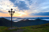 Summer sunset mountain view with christianity cross — Stock Photo