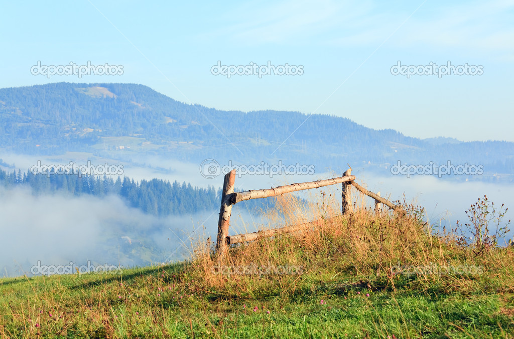 Countryside landscape with wooden fence and mountain behind — Stock Photo #4578048