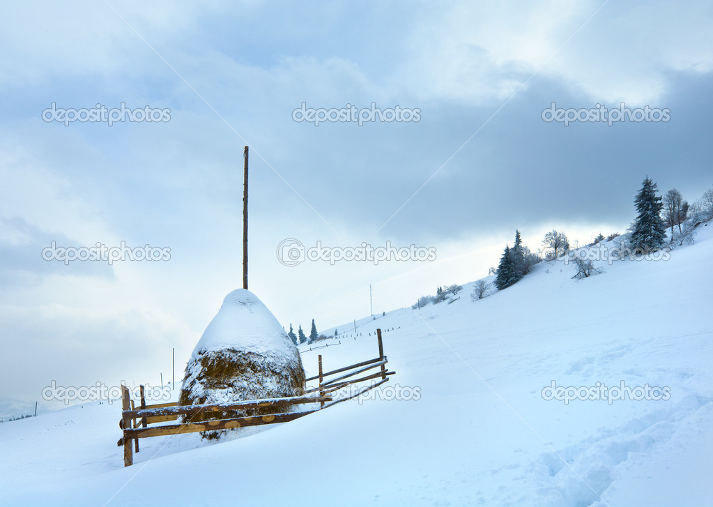 Winter dull country mountain landscape with haystack — Stock Photo #4584170