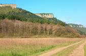 Spring Crimean mountain landscape with road in valley (Mangup Ka — Stock Photo