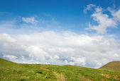 Summer green mountainside and cloudy sky — Stock Photo