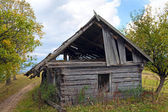 Ruined shed on mountain glade — Stock Photo