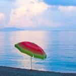 Sunset and sunshade on beach — Stock Photo