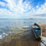Old flooding boat on summer lake shore — Stock Photo #5033545